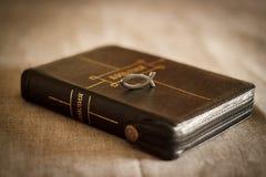 Bild einer Buch Bibelnahaufnahme im schwarzen Ledereinband mit einem Reißverschluss mit einem christlichen hängenden Symbolfisch  Lizenzfreies Stockfoto