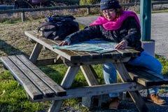Bild einer Frau mit der warmen Kleidung, die das Schauen sitzt oder, überprüft den Weg auf einer Papierkarte stockfoto