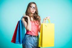 Bild einer jungen Brunettefrau, die eine rosa Spitze und Blue Jeans aufwerfen mit Einkaufstaschen und betrachten Kamera über Blau lizenzfreie stockfotos
