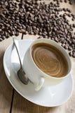 Bild einer Kaffeetasse und untertasse mit einem alten Weinleselöffel auf eine Holztischoberseite umgeben durch die Rohkaffeebohne Lizenzfreie Stockfotografie