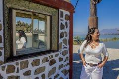 Bild einer lächelnden Frau mit der langen tragenden weißen Kleidung des schwarzen Haares, die über den Spiegel nachdenkt stockbilder