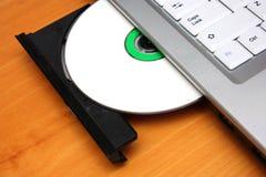 Bild einer optischen Speicherplatte, die in den Antrieb eines Laptops eingefügt wird Stockfotos
