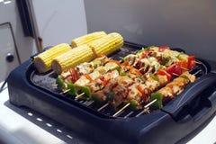 Bild eines elektrischen Grills überstiegen mit Fleisch auf Aufsteckspindeln und Gemüse, die gedient werden, sobald gekocht stockbilder