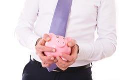 Geschäftsmann, der eine piggy Bank hält. Stockbilder