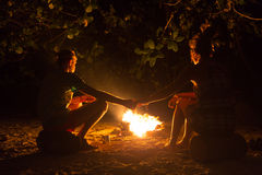 Bild eines großen Lagerfeuers, um das Leute, die in den Bergen nachts sich aalen Lizenzfreies Stockfoto