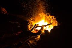 Bild eines großen Lagerfeuers, um das Leute, die in den Bergen nachts sich aalen Stockbild