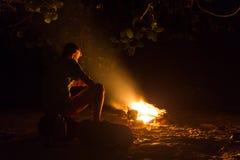 Bild eines großen Lagerfeuers, um das Leute, die in den Bergen nachts sich aalen Lizenzfreie Stockfotografie
