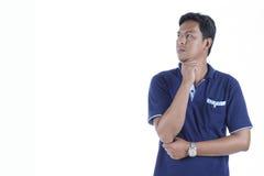 Bild eines jungen Mannes, der, lokalisiert auf weißem Hintergrund denkt Lizenzfreies Stockfoto