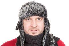 Bild eines jungen Mannes kleidete im Winterhut lächelnd an, lokalisiert Lizenzfreies Stockfoto