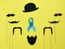 Bild eines Mannes auf Papier Blaues Band des Bartes und des Schnurrbartes Auf gelbem Hintergrund Konzept von Prostatakrebs stockfotografie