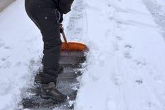Bild eines Mannes in der Winterkleidung, die den Weg von gefallenem Schnee aufräumt Stockfotografie
