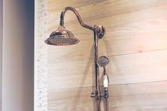 Bild eines modernen Duschkopfspritzens Kupferner Duschkopf, hölzerner Wandhintergrund lizenzfreie stockfotos