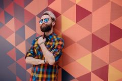 Bild eines modernen jungen Modells, gekleidet in einem Mehrfarbent-shirt, werfend auf einer geometrischen Formwand der Hexagone a stockbild