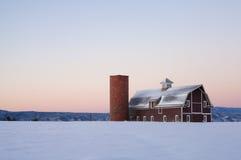 Bild eines roten Stalles mit einem Feld des Schnees Stockbilder