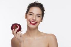 Bild eines schönen Mädchens des Lächelns mit einem roten Apfel Lizenzfreie Stockbilder