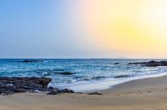 Bild eines Strandes mit einem Segelboot, das den Horizont kreuzt stockfoto