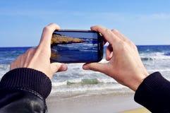 Bild eines Strandes mit einem Smartphone Stockbild