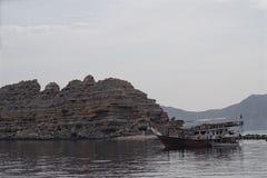 Bild eines traditionellen Bootes, das Dow genannt wurde, machte kurz Kreuzfahrten im cristal Wasser zwischen Klippen stockfotos