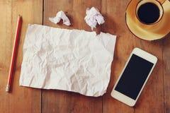 Bild för bästa sikt av den skrynkliga tomt papper, koppen kaffe och smartphonen över trätabellen Arkivfoto
