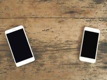 Bild för bästa sikt av smartphone två över trätabellen med kopieringsbrunnsorten Royaltyfri Bild