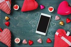 Bild för bästa sikt av smartphonen, färgrika hjärtaformchoklader, tyghjärtor på svart tavlabakgrund Valentin dagberöm Arkivbilder