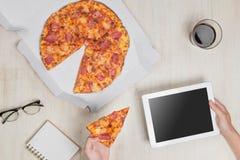Bild för bästa sikt Snabb pizzaleverans Man som äter och använder en tabl Royaltyfri Bild