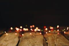 bild för bakgrundsbegreppsenergi tapeter på skrivbordet i stilen för nytt år Träfotobakgrund med girlander och bokeh på svart royaltyfri bild