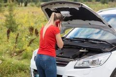Bild för bakre sikt av den unga kvinnan som ser under huven av den brutna bilen och kallar service Arkivbild