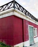 Bild för Colorfull utomhus- grunge för vibrerande röd gammal husperspektiv Royaltyfri Foto