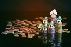 Bild för egenskapsinvestering Creatively tänt grönt hus och staplade mynt mot en svart bakgrund royaltyfria foton