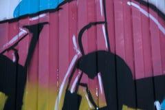 Bild för färg DSLR av mång- färgskriftgrafitti mot en grå tegelstenvägg Bilden är i horisontalriktning med kopieringsspac arkivfoton