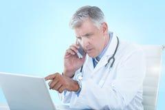 Bild för komposit 3d av den manliga doktorn som pekar på bärbara datorn, medan genom att använda mobiltelefonen Royaltyfri Foto
