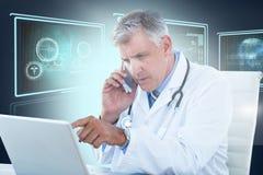 Bild för komposit 3d av den manliga doktorn som pekar på bärbara datorn, medan genom att använda mobiltelefonen Royaltyfria Bilder