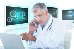 Bild för komposit 3d av den manliga doktorn som pekar på bärbara datorn, medan genom att använda mobiltelefonen Fotografering för Bildbyråer