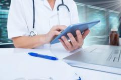 Bild för komposit 3d av midsectionen av den kvinnliga doktorn som använder den digitala minnestavlan Royaltyfri Bild
