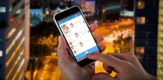 Bild för komposit 3d av närbilden av kantjusterade händer som rymmer mobiltelefonen Royaltyfria Bilder
