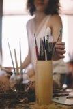 Bild för konstnärflickamålarfärger på kanfas i studio royaltyfria bilder