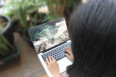 Bild för kvinna- eller flickavisninghav på hennes bärbar dator, hennes nästa semester Arkivbild
