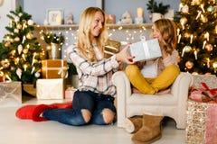 Bild för ` s för nytt år av den lyckliga modern som ger gåvan till dottersammanträde på fåtöljen Arkivbilder