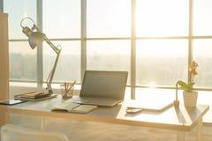 Bild för sidosikt av studioarbetsplatsen med den tomma anteckningsboken, bärbar dator Bekväm arbetstabell, inrikesdepartementet Fotografering för Bildbyråer