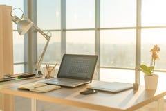 Bild för sidosikt av studioarbetsplatsen med den tomma anteckningsboken, bärbar dator Bekväm arbetstabell, inrikesdepartementet Royaltyfria Foton