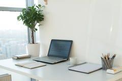 Bild för sidosikt av studioarbetsplatsen med den tomma anteckningsboken, bärbar dator Märkes- bekväm arbetstabell, inrikesdeparte Royaltyfri Bild