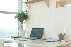 Bild för sidosikt av studioarbetsplatsen med den tomma anteckningsboken, bärbar dator Märkes- bekväm arbetstabell, inrikesdeparte Arkivbilder