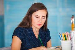 Bild för Yound kvinnamålarfärger med akvareller Arkivbilder