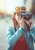 Bild för Hipsterflickadanande med den retro kameran, fokus på kamera Royaltyfri Bild