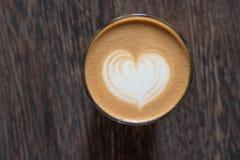 Bild i form en hjärta, i koppen kaffe på en träbakgrund Sort från över arkivfoto