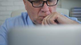 Bild med affärsmanReading Preoccupied Financial information från en bärbar dator arkivbilder