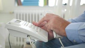 Bild mit dem Mann, der auf einem Stuhl in der Büro-Raum-Gebrauchs-Telefon-Überlandleitungs-Verbindung sitzt stock footage