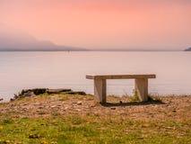 Bild mit Steinbank vor einem See mit Sonnenuntergangansicht stockfotos