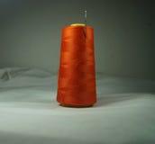 Bild-orange Thread auf Lager mit Nadel lizenzfreie stockfotografie